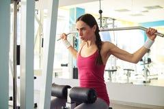 La muchacha en ropa de deportes está resolviendo la máquina del tirón-abajo en gimnasio Imagen de archivo libre de regalías