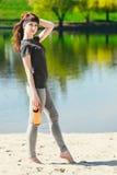 La muchacha en ropa del deporte está sosteniendo una botella de agua, pareciendo ausente y de sonrisa, colocándose en la playa de Imagenes de archivo