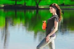 La muchacha en ropa del deporte está sosteniendo una botella de agua, pareciendo ausente y de sonrisa, colocándose en la playa de Imagen de archivo