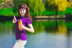 La muchacha en ropa del deporte está sosteniendo una botella de agua, pareciendo ausente y de sonrisa, colocándose en la playa de Foto de archivo