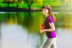 La muchacha en ropa del deporte está sosteniendo una botella de agua, pareciendo ausente y de sonrisa, colocándose en la playa de Foto de archivo libre de regalías