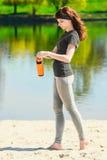 La muchacha en ropa del deporte está sosteniendo una botella de agua, pareciendo ausente y de sonrisa, colocándose en la playa de Fotos de archivo libres de regalías