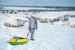La muchacha en ropa del esquí arrastra nieve de la tubería en la colina Imagen de archivo