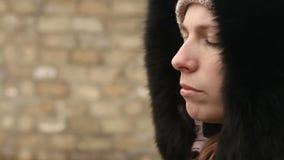 La muchacha en ropa del invierno mastica el bolo alimenticio metrajes