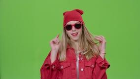 La muchacha en ropa elegante y vidrios rojos liga y guiña Pantalla verde metrajes