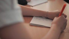 La muchacha en la sala de clase en la escuela escribe palabras en un cuaderno Visión desde el hombro del niño