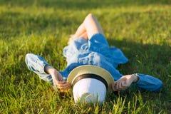 La muchacha en sombrero del vestido y de paja miente en la hierba verde Visión desde arriba Fotografía de archivo libre de regalías