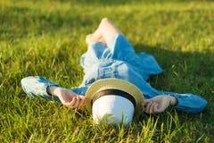 La muchacha en sombrero del vestido y de paja miente en la hierba verde Visión desde arriba Fotografía de archivo