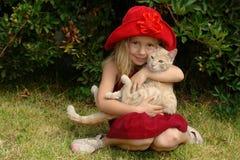La muchacha en sombrero rojo con el gato Fotos de archivo libres de regalías
