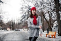 La muchacha en sombrero rojo y la bufanda que caminan en invierno parquean Fotos de archivo libres de regalías