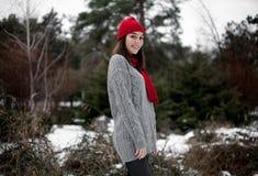 La muchacha en sombrero rojo y la bufanda que caminan en invierno parquean Fotos de archivo
