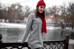 La muchacha en sombrero rojo y la bufanda que caminan en invierno parquean cerca del lago Fotografía de archivo libre de regalías