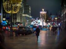 La muchacha en sombrero rosado camina a lo largo de la opinión adornada la Navidad de la calle de Tverskaya del hotel Moscú Imágenes de archivo libres de regalías