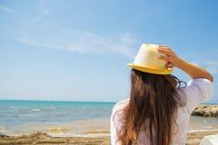 La muchacha en sombrero ve en el mar imagen de archivo