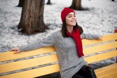 La muchacha en sombrero y bufanda rojos está descansando sobre banco en parque del invierno Imágenes de archivo libres de regalías