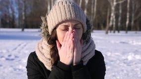 La muchacha en sombrero y chaqueta negra en el invierno estornuda cerca de un bosque, almacen de video