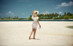 La muchacha en sombrero y el blanco se visten en la playa En la orilla del océano Maldivas, la isla Vacaciones, viaje Imágenes de archivo libres de regalías