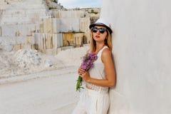 La muchacha en sombrero y vidrios con un ramo de lila florece cerca de la pared blanca de mármol imágenes de archivo libres de regalías