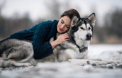 La muchacha en suéter miente y abraza el Malamute de Alaska del perro Fotografía de archivo