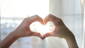 La muchacha en su dormitorio en la ventana coge sus manos, hechas bajo la forma de corazón, los rayos del ` s del sol Bokeh