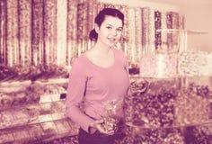 La muchacha en tienda está cogiendo los caramelos Fotografía de archivo libre de regalías