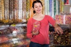 La muchacha en tienda está cogiendo los caramelos Imágenes de archivo libres de regalías