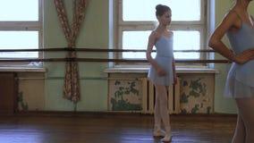 La muchacha en traje azul del ballet se coloca en la tercera posición wating para que el ejercicio comience y escuche el ballet d almacen de metraje de vídeo