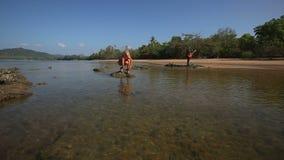 La muchacha en traje de baño se pone en cuclillas en roca en juegos del mar y del guitarrista almacen de metraje de vídeo