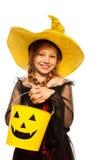 La muchacha en traje de la bruja y Halloween fantasmagórico bucket Fotografía de archivo libre de regalías