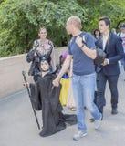 La muchacha en traje del carnaval camina con los padres Fotos de archivo