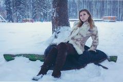 La muchacha en un abrigo de pieles corto beige y botas marrones con el pelo que fluye se est? sentando en la nieve cerca del ?rbo imagen de archivo