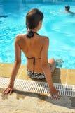 La muchacha en un bañador se sienta en el borde de la piscina Fotografía de archivo