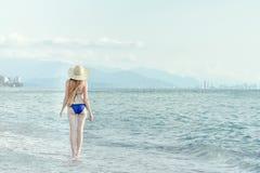 La muchacha en un bañador y un sombrero camina por el mar Visión desde la parte posterior imagen de archivo