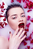 La muchacha en un baño con los pétalos color de rosa Imágenes de archivo libres de regalías