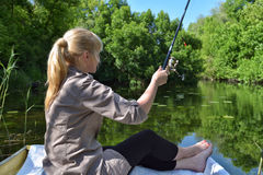 La muchacha en un barco está pescando en el lago Imagen de archivo libre de regalías