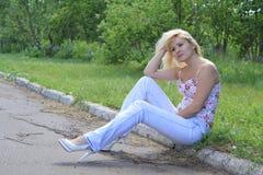 La muchacha en un borde de la carretera del camino piensa adonde ir Foto de archivo
