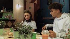 La muchacha en un café lee ruidosamente un momento interesante del libro de la ficción, y su amigo pasa una manzana jugosa a un a almacen de video