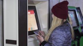 La muchacha en un cajero automático utiliza una tarjeta metrajes