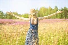 La muchacha en un campo disfruta en el sol Fotografía de archivo