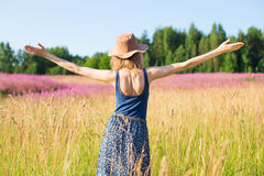 La muchacha en un campo disfruta en el sol Fotos de archivo
