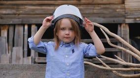 La muchacha en un casco protector de un constructor o de un ingeniero juega a un super héroe almacen de video