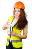 La muchacha en un casco y un chaleco mira en el envase abierto del metal Foto de archivo