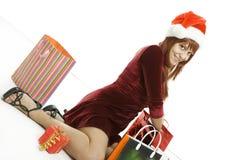 La muchacha en un casquillo de la Navidad con las compras Fotos de archivo libres de regalías