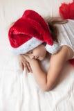 La muchacha en un casquillo del Año Nuevo duerme antes de Año Nuevo Imágenes de archivo libres de regalías