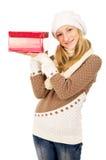 La muchacha en un casquillo del invierno señala al regalo Imágenes de archivo libres de regalías