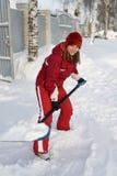 La muchacha en un casquillo del invierno y una chaqueta tiene control Imágenes de archivo libres de regalías