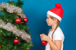 La muchacha en un casquillo rojo cuelga para arriba un juguete en un abeto Imagen de archivo