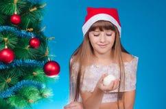 La muchacha en un casquillo rojo se sienta cerca de un árbol del Año Nuevo y de HOL elegantes Imagenes de archivo