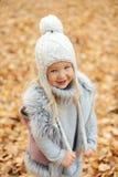 La muchacha en un casquillo y las hojas de otoño que se colocan en otoño parquean por la tarde Imagen de archivo
