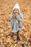 La muchacha en un casquillo y las hojas de otoño que se colocan en otoño parquean por la tarde Imágenes de archivo libres de regalías